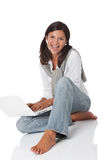 Smiling teenager sitting with laptop Royalty Free Stock Image