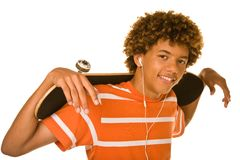 Smiling teenager with skateboard and earbuds Royalty Free Stock Photography