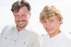 Smiling teenager son with father outdoor summer. Smiling teenager son with father outdoor royalty free stock image