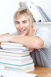 Smiling teenager studying a lot of books Stock Photo