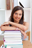 Smiling teenager studying lots of books Royalty Free Stock Photography