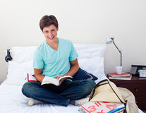 Smiling teenager studying maths in his bedroom. Sitting on his bed Royalty Free Stock Photography