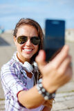 Smiling teenager taking picture with smartphone Stock Photography