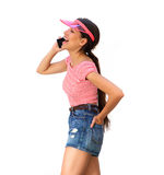 Smiling teenager walking and talking with mobile phone Royalty Free Stock Images