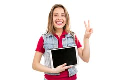 Smiling teenager woman with tablet gesturing at camera royalty free stock photos