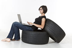 Smiling teenager working on computer. Smiling young girl is sitting on tires working on laptop isolated on white Stock Image