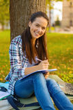Smiling teenager writing in notebook. Education, campus and people concept - smiling teenager writing in notebook Royalty Free Stock Photography