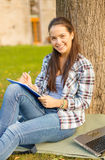 Smiling teenager writing in notebook Royalty Free Stock Photo