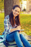Smiling teenager writing in notebook Stock Photo
