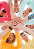 Smiling teenagers with hands on top of each other. Friendship, youth and people concept - group of smiling teenagers with hands on top of each other Stock Photography