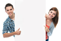 Smiling teenagers holding at a blank board. Two smiling teenagers holding at a blank board Royalty Free Stock Photography
