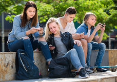 Smiling teenagers playing with mobile phones