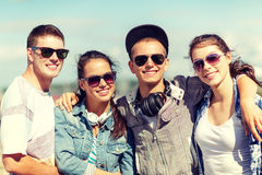 Smiling teenagers in sunglasses hanging outside Royalty Free Stock Images