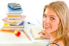 Smiling teengirl sitting at table with books Royalty Free Stock Photos