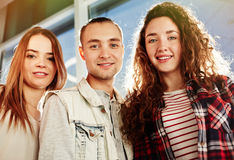 Smiling teens. Three young friends in casual-wear looking at camera Stock Photo
