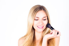 Smiling with teeth woman holding brush for rouge looks down. Happy smiling with teeth woman holding brush for rouge looks down Stock Photo