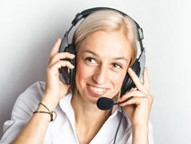 Smiling telephonist. Young telephonist at work - bright background Stock Photos
