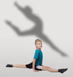Smiling boy doing horizontal splits with dancer's silhouette behind him. Smiling ten-year-old boy doing horizontal splits with dancer's silhouette behind him, on royalty free stock images