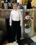 Smiling ten-year-old girl standing next to a picture of a snowman. Smiling ten-year-old girl in a diner standing next to a picture of a snowman dressed in Stock Photography
