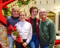 Smiling ten-year-old girl standing on a red stairway with elderly grandfather and sisters Stock Photos