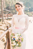 Smiling tender bride with beautiful bouquet Royalty Free Stock Photography