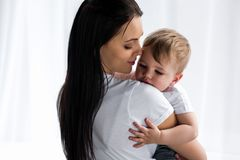 Smiling tender mother holding cute baby boy. In hands at home royalty free stock photo