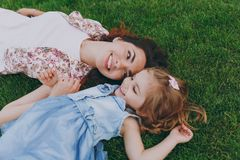 Smiling tender woman in light dress and little cute child baby girl lie on green grass in park rest, have fun. Mother. Smiling tender women in light dress and royalty free stock image