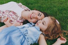 Smiling tender woman in light dress and little pretty child baby girl lie on green grass in park rest, have fun. Mother. Smiling tender women in light dress and stock photography