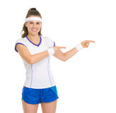 Smiling tennis player pointing on copy space Royalty Free Stock Images