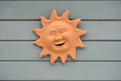 Smiling terracotta sun face Stock Photo