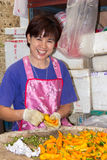 Smiling Thai woman. Bangkok, Thailand-Sep 25th 2012: Smiling woman sorting chillies in Pak Khlong Talad vegetable market. This is the largest wholesale fruit and stock images