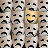 Smiling theater mask in a crowd of sad masks Royalty Free Stock Images