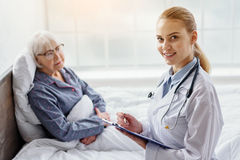 Smiling therapeutic advising old woman in clinic Stock Image
