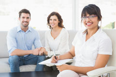 Smiling therapist with patients looking at camera Stock Photography