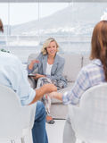 Smiling therapist speaking a couple. During therapy session Stock Images