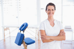 Smiling therapist standing with arms crossed. In medical office Royalty Free Stock Images