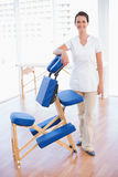Smiling therapist standing with massage chair. In medical office stock image