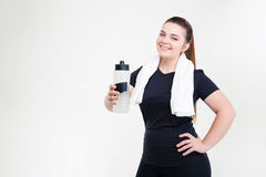 Smiling thick woman in sportswear holding shaker Stock Images