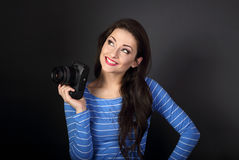 Smiling thinking young female photograph holding photo camera an Royalty Free Stock Images