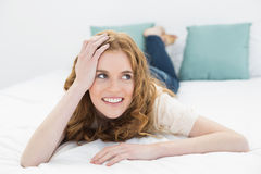 Smiling thoughtful pretty woman in bed Royalty Free Stock Image