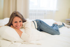 Smiling thoughtful pretty woman lying in bed at home royalty free stock image