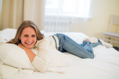 Smiling thoughtful pretty woman lying in bed at home Royalty Free Stock Images