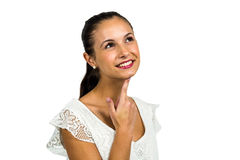 Smiling thoughtful woman with finger on chin Stock Photos