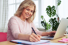 Smiling thoughtful woman writing while working in laptop Royalty Free Stock Images