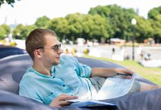 Smiling thoughtful young man in sunglasses laying on a cushion o. Utdoors, holding documents in his hands, education or break from work concept royalty free stock photo