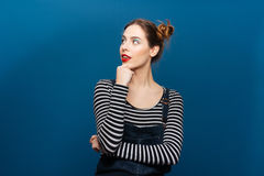 Smiling thoughtful young woman looking away. Over blue background Royalty Free Stock Photography