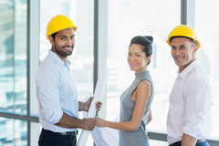Smiling three architects standing in office with blueprint. Portrait of smiling three architects standing in office with blueprint in office Royalty Free Stock Images