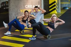 Smiling three people are training with equipment indoors royalty free stock images