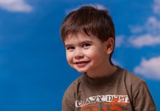 Smiling three year old boy. Portrait on blue sky background Stock Image