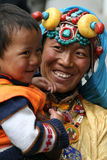 A smiling tibetan lady with her son Stock Image
